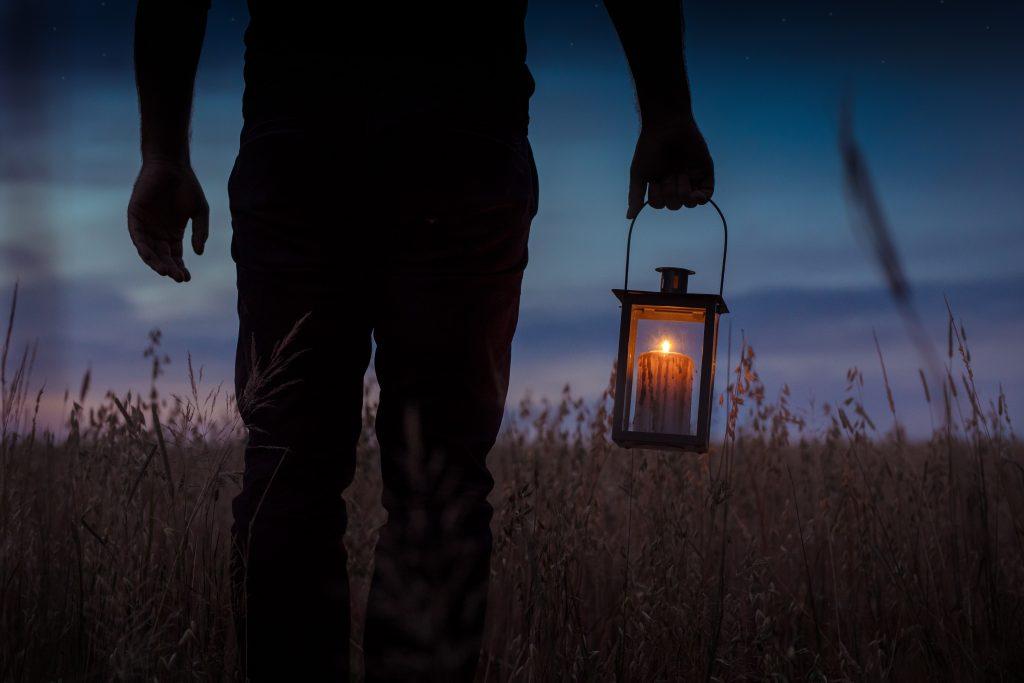 Man holding lantern - Photo by Julia Florczak via unsplash